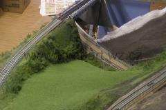 Násep s vysokou trávou a keři. Dole sekaná louka.