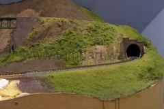 Výjezd z tunelu jednokolejné trati před hlavní mosty a hlavní stanicí.